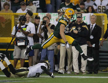 GREEN BAY, WI - SEPTEMBER 08: Jordy Nelson #87 of the Green Bay Packers leaps over Tracy Porter #22 of the New Orleans Saints during the NFL opening season game at Lambeau Field on September 8, 2011 in Green Bay, Wisconsin. The Packers defeated the Saints