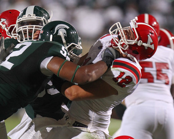 EAST LANSING, MI - SEPTEMBER 02:  Aronde Stanton #52 of the Michigan State Spartans gets his hands up in the face of Kurt Hess #12 of the Youngstown State Penguins during an NCAA football game at Spartan Stadium on September 2, 2011 in East Lansing, Michi