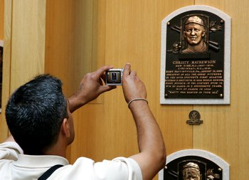 A fan snaps a shot of Christy Mathewson's Hall of Fame plaque.