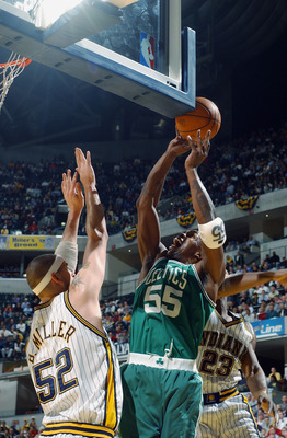 INDIANAPOLIS - APRIL 21:  Eric Williams #55 of the Boston Celtics shoots against Brad Miller #52 and Ron Artest #23 of the Indiana Pacers in Game two of the Eastern Conference Quarterfinals against the during the 2003 NBA Playoffs at Conseco Fieldhouse on