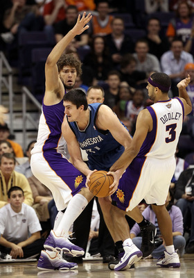 PHOENIX - DECEMBER 15:  Darko Milicic #31 of the Minnesota Timberwolves attempts to pass the ball against Robin Lopez of the Phoenix Suns during the NBA game at US Airways Center on December 15, 2010 in Phoenix, Arizona. NOTE TO USER: User expressly ackno