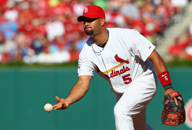 ST. LOUIS, MO -SEPTEMBER 5:  Albert Pujols #5 of the St. Louis Cardinals flips the ball to first base against the Milwaukee Brewers at Busch Stadium on September 5, 2011 in St. Louis, Missouri.  (Photo by Dilip Vishwanat/Getty Images)