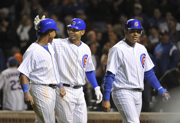 CHICAGO, IL - SEPTEMBER 07:  Starlin Castro #13 of the Chicago Cubs along with teammates Carlos Pena #22 and Aramis Ramirez #16 walk back to the dugout after Pena hit a three-run home run scoring Ramirez and Castro during the eighth inning against the Cin