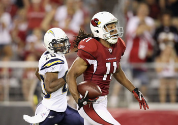 GLENDALE, AZ - AUGUST 27:  Wide receiver Larry Fitzgerald #11 of the Arizona Cardinals runs with the ball on a 80 yard touchdown reception past cornerback Antoine Cason #20 of the San Diego Chargers during the first quarter of the preseason NFL game at th