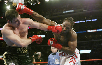 LOS ANGELES - JUNE 21:  Vitali Klitschko (left) hits Lennox Lewis (right) during their WBC and IBO World Heavyweight Championship bout at the Staples Center on June 21, 2003 in Los Angeles, California.  Lennox Lewis (41-2-1) defeated Vitali Klitschko (32-