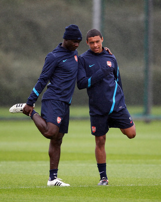 ST ALBANS, ENGLAND - AUGUST 23:  Emmanuel Frimpong (L) and Alex Oxlade-Chamberlain of Arsenal  stretch during a training session ahead of their UEFA Champions League Qualifying second leg match against Udinese at London Colney on August 23, 2011 in St Alb