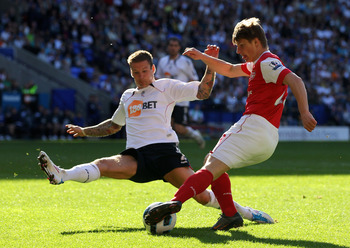 BOLTON, ENGLAND - APRIL 24:  Gretar Steinsson of Bolton Wanderers competes with Andrey Arshavin of Arsenal during the Barclays Premier League match between Bolton Wanderers and Arsenal at the Reebok Stadium on April 24, 2011 in Bolton, England.  (Photo by