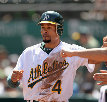 OAKLAND, CA - SEPTEMBER 07:  Coco Crisp #4 of the Oakland Athletics is congratulated by teammates after he scored in the first inning of their game against the Kansas City Royals at O.co Coliseum on September 7, 2011 in Oakland, California.  (Photo by Ezr
