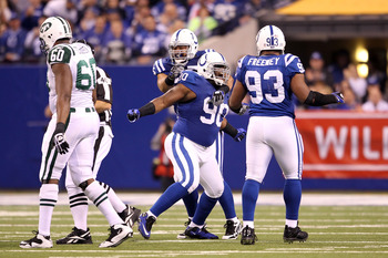 INDIANAPOLIS, IN - JANUARY 08:  Dan Muir #90 of the Indianapolis Colts celebrates with Dwight Freeney #93, and Fili Moala #95 after he sacked quarterback Mark Sanchez #6 of the New York Jets in the first quarter during their 2011 AFC wild card playoff gam