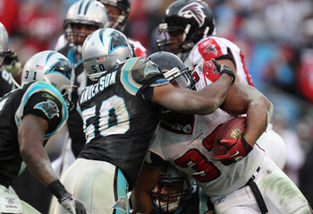 CHARLOTTE, NC - DECEMBER 12:  Michael Turner #33 of the Atlanta Falcons is tackled by James Anderson #50 of the Carolina Panthers during their game at Bank of America Stadium on December 12, 2010 in Charlotte, North Carolina.  (Photo by Streeter Lecka/Get