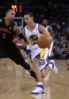 OAKLAND, CA - MARCH 25: Stephen Curry #30 of the Golden State Warriors drives on Jerryd Bayless #5 of the Toronto Raptors at Oracle Arena on March 25, 2011 in Oakland, California. NOTE TO USER: User expressly acknowledges and agrees that, by downloading a