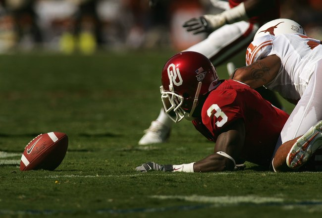 DALLAS - OCTOBER 7:  Reggie Smith #3 of the Oklahoma Sooners fumbles after the tackle by Erick Jackson #21 of the Texas Longhorns during the Red River Shootout at the Cotton Bowl on October 7, 2006 in Dallas, Texas. The Longhorns won 28-10. (Photo by Rona