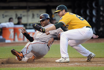 OAKLAND, CA -  JUNE 17: Pablo Sandoval #48 of the San Francisco Giants tries to score on a wild pitch and is tagged out at home plate by Graham Godfrey #65 of the Oakland Athletics during a MLB baseball game June 17, 2011 at the Oakland-Alameda County Col