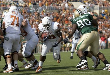 WACO, TX - NOVEMBER 14:  Running back Cody Johnson #31 of the Texas Longhorns carries the ball into the end zone during the first half against tackle Nicolas Jean-Baptiste #90 of the Baylor Bears on November 14, 2009 at Floyd Casey Stadium in Waco, Texas.