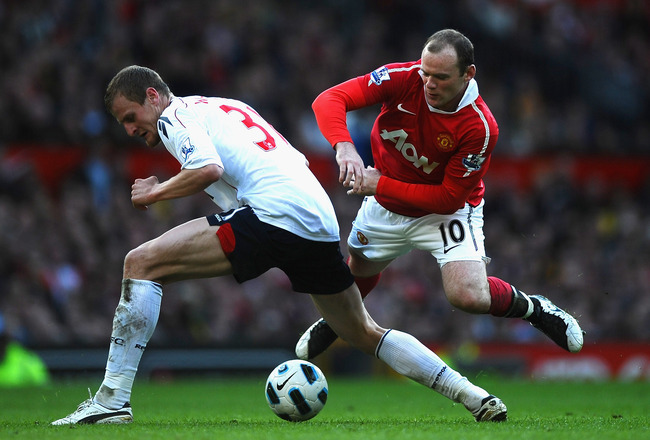 MANCHESTER, ENGLAND - MARCH 19: Wayne Rooney of Manchester United battles with David Wheater of Bolton Wanderers during the Barclays Premier League match between Manchester United and Bolton Wanderers at Old Trafford on March 19, 2011 in Manchester, Engla