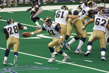 03 Feb 2002:  Quarterback Kurt Warner #13 of the St.Louis Rams  reaches for a hand off to teammate Marshall Faulk #28 during the game against the New England Patriots at Superbowl XXXVI at the Superdome in New Orleans, Louisiana.  The Patriots defeated th