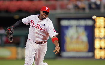 PHILADELPHIA , PA - SEPTEMBER 07:  Ryan Howard #6 of the Philadelphia Phillies makes a bare handed throw toward pitcher Roy Oswalt against the Atlanta Braves at Citizens Bank Park on September 7, 2011 in Philadelphia, Pennsylvania.  The Phillies defeated
