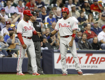 MILWAUKEE, WI - SEPTEMBER 8:  Jaun Samuel #12, third base coach for the Philadelphia Phillies celebrates with Ben Francisco #10 after Francisco advanced to third base on a fielding error by Corey Hart of the Milwaukee Brewers  during their game at Miller