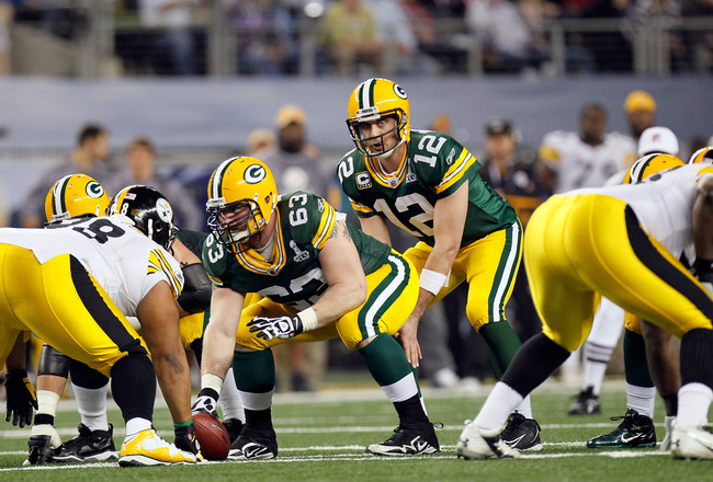 ARLINGTON, TX - FEBRUARY 06:  Aaron Rodgers #12 of the Green Bay Packers calls signals at the line of scrimmage under center Scott Wells #63 against the Pittsburgh Steelers during Super Bowl XLV at Cowboys Stadium on February 6, 2011 in Arlington, Texas.