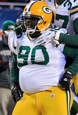 CHICAGO, IL - JANUARY 23:  B.J. Raji #90 of the Green Bay Packers reacts with teammate Sam Shields #37 after scoring on a 18-yard interception return for a touchdown in the fourth quarter against the Chicago Bears in the NFC Championship Game at Soldier F