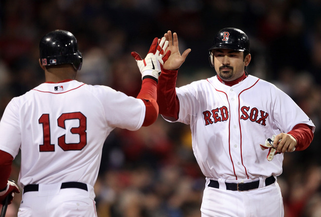 BOSTON, MA - MAY 22:  Adrian Gonzalez #28 of the Boston Red Sox is congratulated by teammate Carl Crawford #13 after Gonzalez scored in the fourth inning against the Chicago Cubs on May 22, 2011 at Fenway Park in Boston, Massachusetts.  Before this series