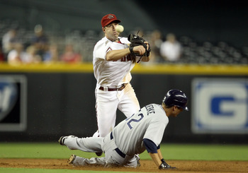 PHOENIX, AZ - SEPTEMBER 08:  Infielder Willie Bloomquist #18 of the Arizona Diamondbacks throws over the sliding Cory Luebke #52 of the San Diego Padres to complete a double play during the third inning of the Major League Baseball game at Chase Field on