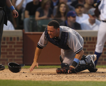 CHICAGO, IL - JUNE 19:  Russell Martin #55 of the New York Yankees hits the ground after being hit in the side of the face by a foul ball against the Chicago Cubs at Wrigley Field on June 19, 2011 in Chicago, Illinois.  (Photo by Jonathan Daniel/Getty Ima
