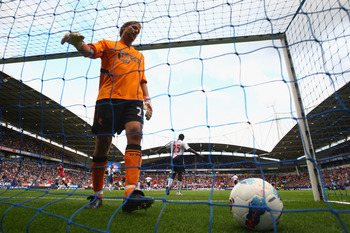 BOLTON, ENGLAND - SEPTEMBER 10:  Jussi Jaaskelainen of  Bolton Wanderers retrieves the ball from the net after Wayne Rooney had scored the third goal for Manchester United during the Barclays Premier League at the Reebok Stadium on September 10, 2011 in B