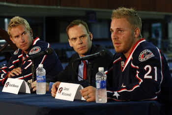COLUMBUS,OH - JULY 21:  General Manager Scott Howson of the Columbus Blue Jackets listens as James Wisniewski #21 of the Columbus Bllue Jackets speaks during a press conference on July 21, 2011 at Nationwide Arena in Columbus, Ohio.  (Photo by John Griesh