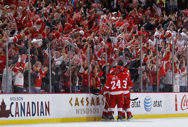 DETROIT - MAY 10:  Ruslan Salei #24 of the Detroit Red Wings celebrates a third period goal by Valtteri Filppula #51 with teammates while playing the San Jose Sharks in Game Six of the Western Conference Semifinals during the 2011 NHL Stanley Cup Playoffs
