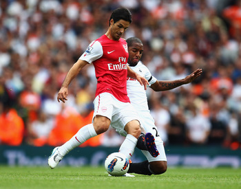 LONDON, ENGLAND - SEPTEMBER 10:  Mikel Arteta if Arsenal is tackled by Kemy Agustien of Swansea City of Swansea City during the Barclays Premier League match between Arsenal and Swansea City at Emirates Stadium on September 10, 2011 in London, England.  (