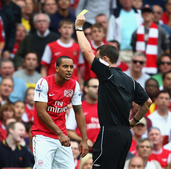 LONDON, ENGLAND - SEPTEMBER 10:  Theo Walcott of Arsenal reacts as he is shown a yellow card by referee Stuart Attwell during the Barclays Premier League match between Arsenal and Swansea City at Emirates Stadium on September 10, 2011 in London, England.