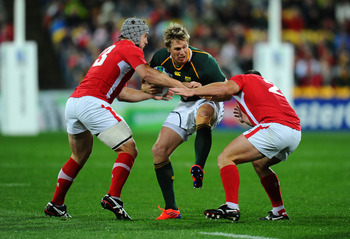WELLINGTON, NEW ZEALAND - SEPTEMBER 11:  Jean de Villiers of South Africa is tackled by Jonathan Davies (L) and Huw Bennett (R) of Wales during the IRB 2011 Rugby World Cup Pool D match between South Africa and Wales on September 11, 2011 in Wellington, N