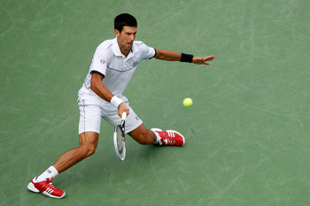 NEW YORK, NY - SEPTEMBER 10:  Novak Djokovic of Serbia hits a return against Roger Federer of Switzerland during Day Thirteen of the 2011 U.S. Open at the USTA Billie Jean King National Tennis Center on September 10, 2011 in the Flushing neighborhood of t