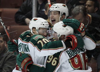 ANAHEIM, CA - FEBRUARY 25:  (L-R) Antti Miettinen #20, Brent Burns #8 and Pierre-Marc Bouchard #96 of the Minnesota Wild celebrate Bouchard's game winning goal in overtime against the Anaheim Ducks at Honda Center on February 25, 2011 in Anaheim, Californ