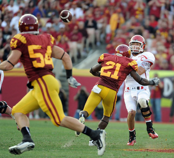 LOS ANGELES, CA - SEPTEMBER 10:  Jordan Wynn #3 of the Utah Utes throws the ball away as he is rushed by Nickell Robey #21 of the USC Trojans during the third quarter at Los Angeles Memorial Coliseum on September 10, 2011 in Los Angeles, California.  (Pho
