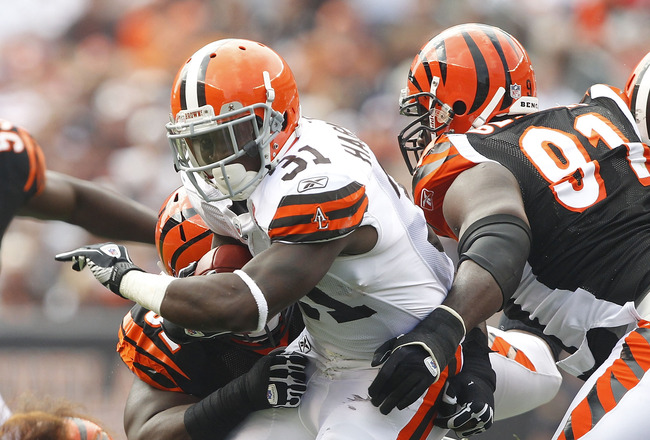 CLEVELAND, OH - SEPTEMBER 11:  Montario Hardesty #31 of the Cleveland Browns runs the ball by defensive end Robert Geathers #91 of the Cincinnati Bengals during the season opener at Cleveland Browns Stadium on September 11, 2011 in Cleveland, Ohio.  (Phot