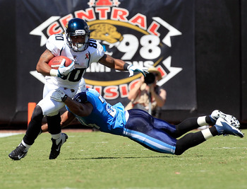 JACKSONVILLE, FL - SEPTEMBER 11:   Mike Thomas #80 of the Jacksonville Jaguars runs for yardage past  Chris Hope #24 of the Tennessee Titans following a reception during the season opener game at EverBank Field on September 11, 2011 in Jacksonville, Flori