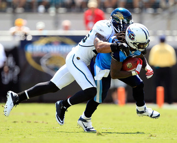 JACKSONVILLE, FL - SEPTEMBER 11:   Dawan Landry #26 of the Jacksonville Jaguars tackles  Chris Johnson #28 of the Tennessee Titans during the season opener game at EverBank Field on September 11, 2011 in Jacksonville, Florida.  (Photo by Sam Greenwood/Get