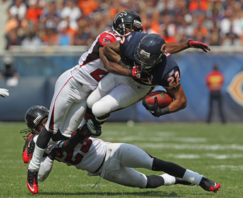 CHICAGO, IL - SEPTEMBER 11:  Matt Forte #22 of the Chicago Bears is tripped up by Dunta Robinson #23 and Chris Owens #21 of the Atlanta Falcons at Soldier Field on September 11, 2011 in Chicago, Illinois. The Bears defeated the Falcons 30-12. (Photo by Jo