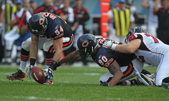 CHICAGO, IL - SEPTEMBER 11: Brian Urlacher #54 of the Chicago Bears pics up a fumble that's out of the reach of teammate Julius Peppers #90 as Sam Baker #72 of the Atlanta Falcons holds back Peppers at Soldier Field on September 11, 2011 in Chicago, Illin