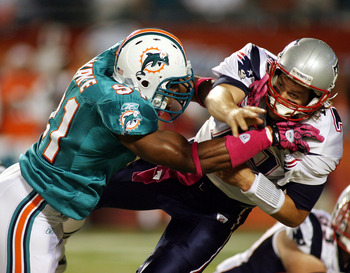 MIAMI - OCTOBER 04:  Quarterback Tom Brady #12 of the New England Patriots is preasures by linebacker Cameron Wake #91 of the Miami Dolphins at Sun Life Stadium on October 4, 2010 in Miami, Florida.  (Photo by Marc Serota/Getty Images)