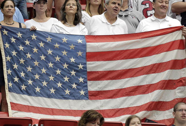 HOUSTON - SEPTEMBER 11:  Fans wave an American flag during a football game between the Indianapolis Colts and the Houston Texans during the season-opening game  at Reliant Stadium on September 11, 2011 in Houston, Texas.  (Photo by Bob Levey/Getty Images)