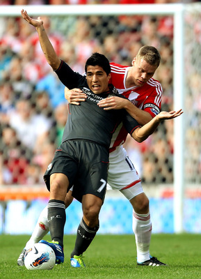 STOKE ON TRENT, ENGLAND - SEPTEMBER 10:  Luis Suarez of Liverpool (L) holds off Ryan Shawcross of Stoke during the Barclays Premier League match between Stoke City and Liverpool at Britannia Stadium on September 10, 2011 in Stoke on Trent, England.  (Phot