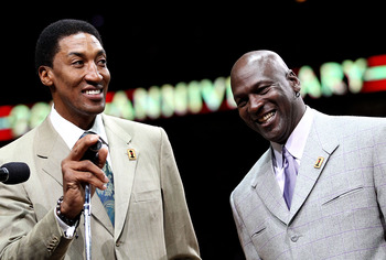 CHICAGO, IL - MARCH 12: Former players Scottie Pippen and Michael Jordan of the Chicago Bulls smile as the crowd cheers during a 20th anniversary recognition ceremony of the Bulls 1st NBA Championship in 1991 during half-time of a game bewteen the Bulls a