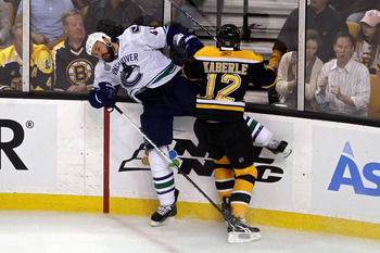BOSTON, MA - JUNE 13:  Andrew Alberts #41 of the Vancouver Canucks collides with Tomas Kaberle #12 of the Boston Bruins during Game Six of the 2011 NHL Stanley Cup Final at TD Garden on June 13, 2011 in Boston, Massachusetts.  (Photo by Bruce Bennett/Gett