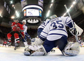 NEWARK, NJ - APRIL 06: Jean-Sebastien Giguere #35 of the Toronto Maple Leafs blocks the net as Brian Rolston #12 of the New Jersey Devils takes a hit at the Prudential Center on April 6, 2011 in Newark, New Jersey. The Devils defeated the Maple Leafs 4-2.