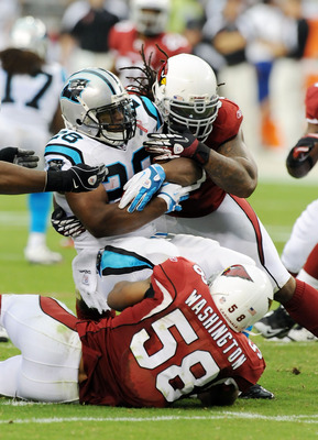 GLENDALE, AZ - SEPTEMBER 11:  Jonathan Stewart #28 of the Carolina Panthers gets tackled by Darnell Dockett #90 of the Arizona Cardinals in the NFL season opening game at the University of Phoenix Stadium on September 11, 2011 in Glendale, Arizona.  (Phot