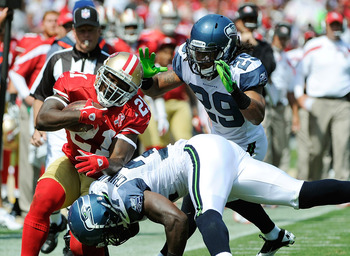 SAN FRANCISCO, CA - SEPTEMBER 11: Frank Gore #21 of the San Francisco 49ers gets knocked out of bounds by Kam Chancellor #31 of the Seattle Seahawks in the first quarter of the season-opening game at Candlestick Park on September 11, 2011 in San Francisco