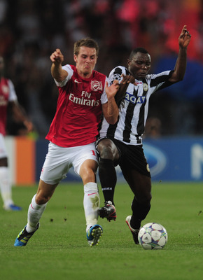 UDINE, ITALY - AUGUST 24:  Aaron Ramsey of Arsenal battles with Kwadwo Asamoah of Udinese during the UEFA Champions League play-off second leg match between Udinese Calcio and Arsenal FC at the Stadio Friuli on August 24, 2011 in Udine, Italy.  (Photo by